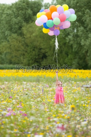 girl holding bunch of balloons among