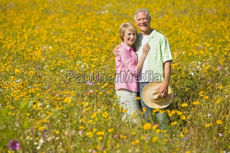portrait of smiling couple among wildflowers