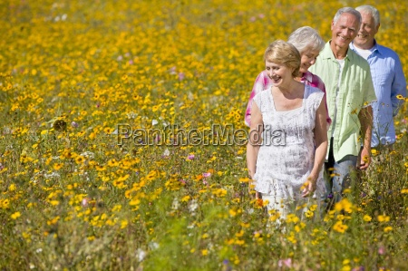 smiling couples walking among wildflowers in