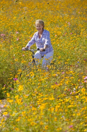 smiling woman riding bicycle among wildflowers