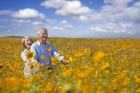 smiling couple riding bicycle among wildflowers