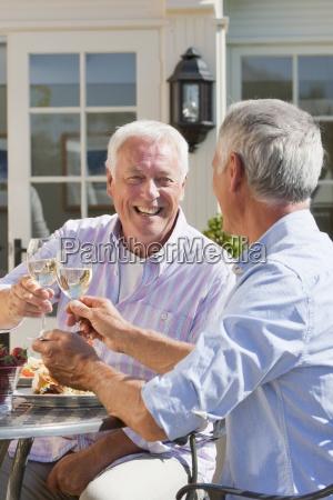 smiling senior men drinking wine on