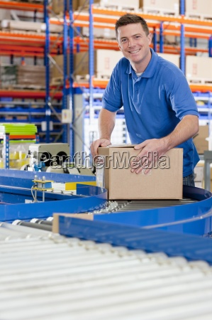 portrait of smiling worker with cardboard