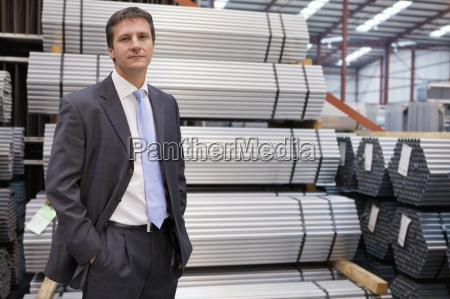 portrait of confident businessman near stacked