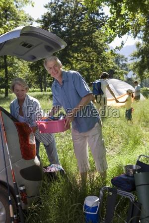 multi generational family unloading car on