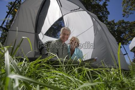 senior couple sitting inside tent smiling