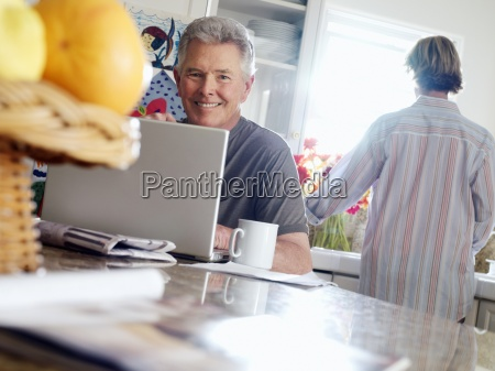 senior man using laptop at breakfast