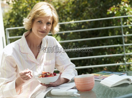 woman sitting at balcony table eating