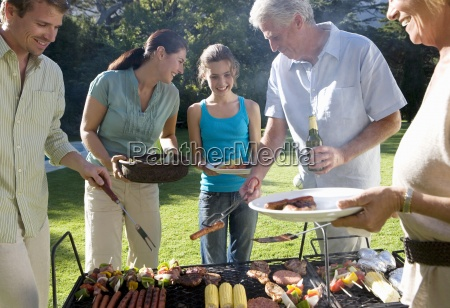 three generation family standing beside barbecue