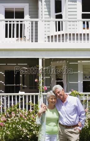 senior couple standing in summer garden