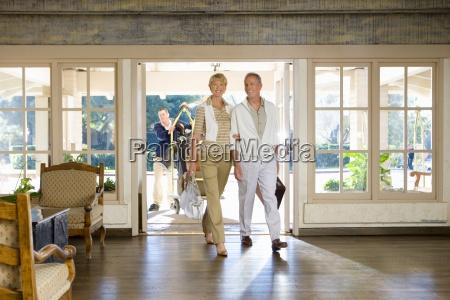 mature couple entering hotel foyer smiling