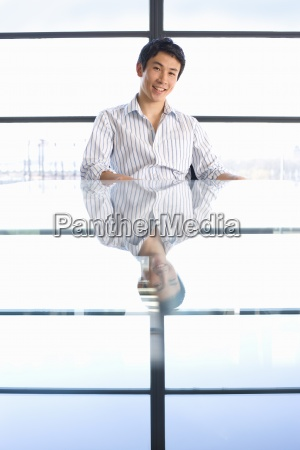 young man sitting at glass table