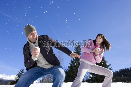 young couple having snow filght in