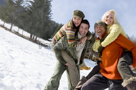 two young couples in snow men