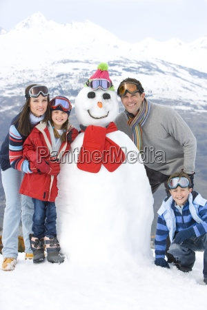 family of four standing by snowman