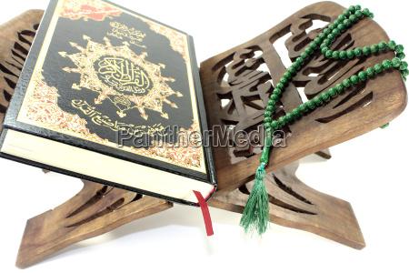 koranstaender mit koran und gruenem rosenkranz