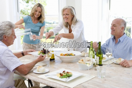 two mature couples at dinner table