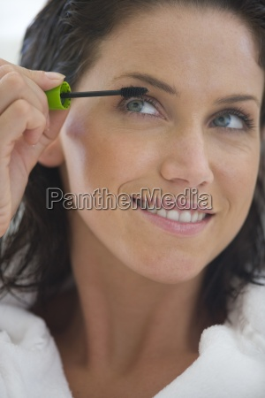 young woman applying mascara smiling close