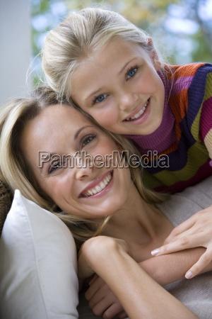daughter 10 12 embracing mother smiling