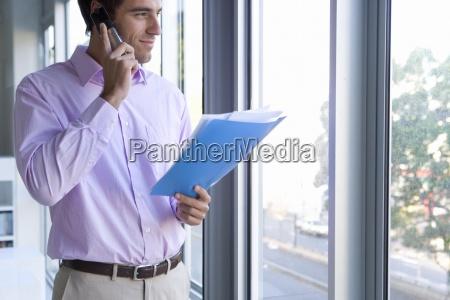 businessman holding paperwork using telephone looking