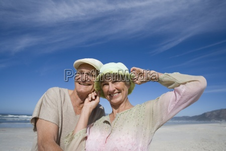 senior couple in hats on beach
