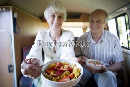 senior couple eating breakfast in back