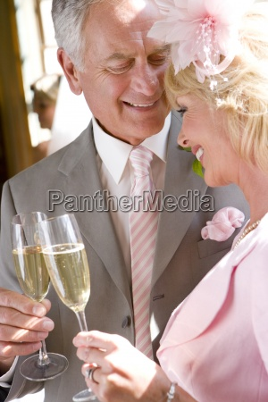 senior bride and groom with champagne