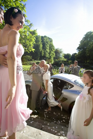 bride and groom by car bridesmaid