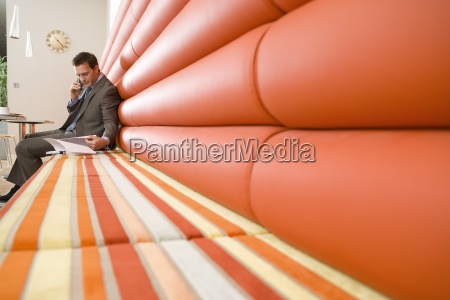 businessman in booth using mobile phone