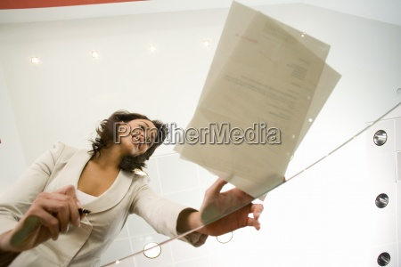 woman signing paperwork on glass table