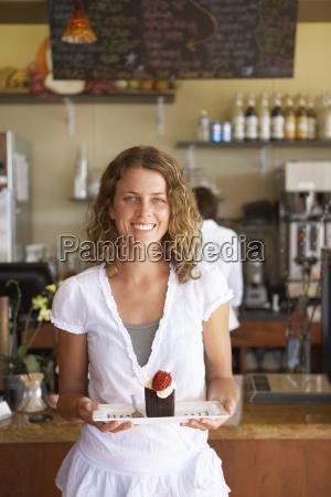 kellnerin arbeitet hinter zaehler im cafe