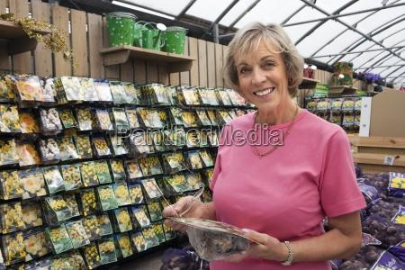 senior woman holding flower bulbs in