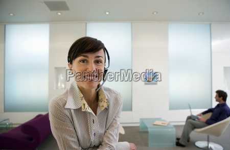 businesswoman wearing telephone headset leaning on