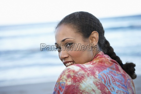 woman standing on beach looking over