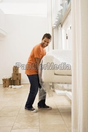 man umzug weissen sofa in plastikfolie