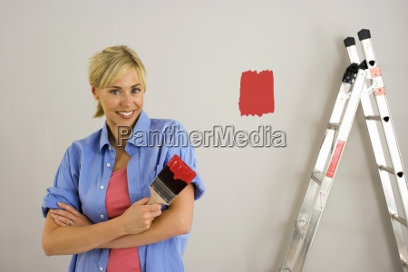 woman decorating at home painting wall