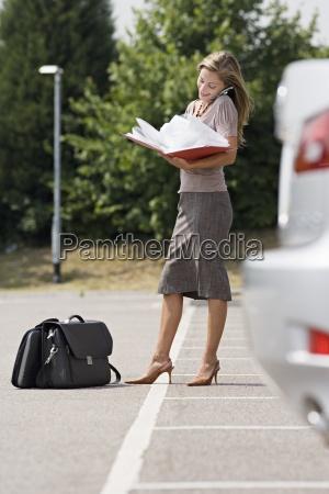 geschaeftsfrau auf dem parkplatz stehen lesen