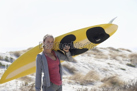 young woman carrying yellow surfboard on