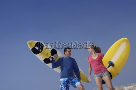 young couple carrying surfboards on beach