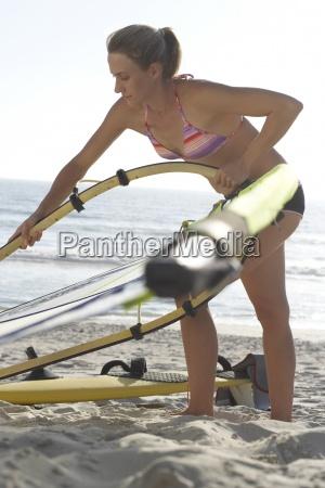 young woman in bikini assembling windsurfer