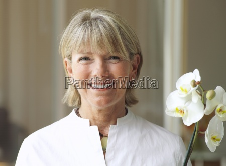 senior woman holding flower smiling front