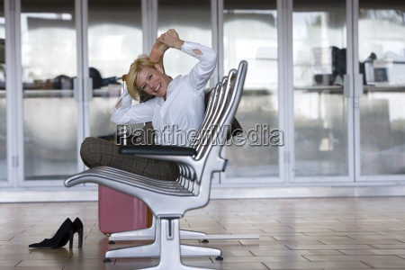 geschaeftsfrau stretching im flughafen wartebereich
