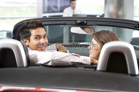 couple sitting in convertible in car