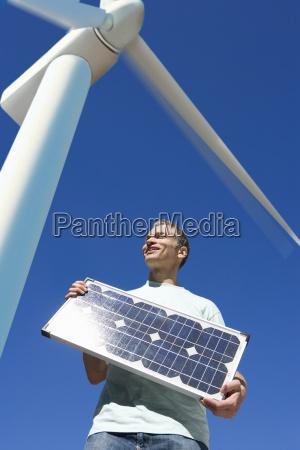mann haelt solarzelle unter windmuehle