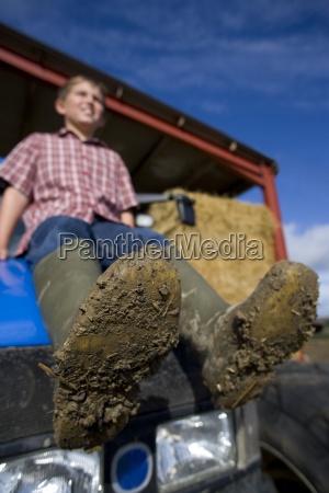 junge sitzt auf traktor mit schmutzigen