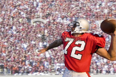 quarterback throwing football with crowd in