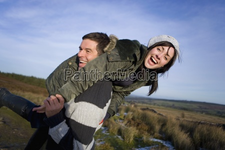man lifting woman over shoulder in