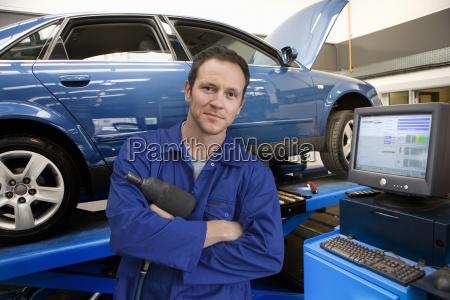 mechaniker in autowerkstatt neben dem computer