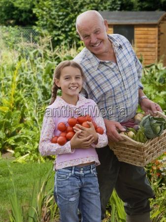 grossvater und enkelin sammeln gemuese im