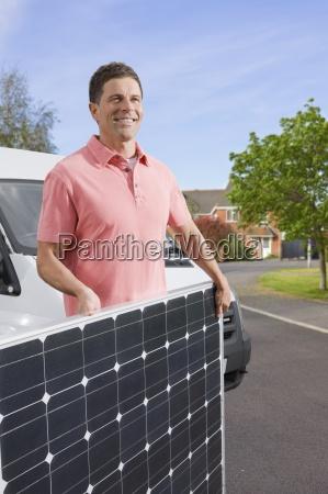 mann mit solar panel auf der